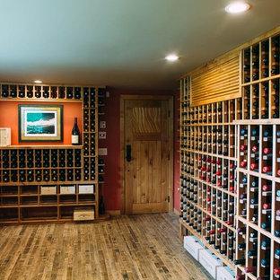 Foto de bodega bohemia, grande, con suelo de madera clara y botelleros