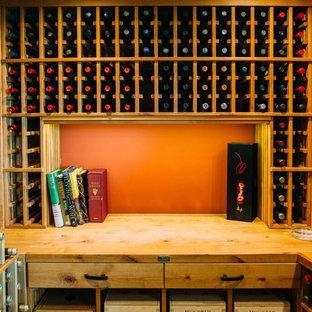 Imagen de bodega bohemia, grande, con suelo de madera clara y botelleros