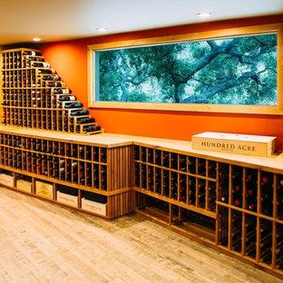 Ejemplo de bodega ecléctica, grande, con suelo de madera clara y botelleros