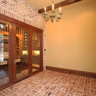 Cette image montre une cave à vin traditionnelle de taille moyenne avec un sol en brique, un présentoir et un sol rouge.