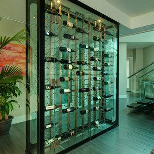 Mid-sized minimalist medium tone wood floor and brown floor wine cellar photo in Vancouver with display racks