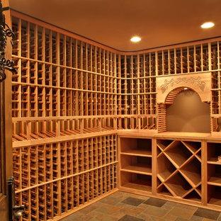 Idée de décoration pour une cave à vin tradition de taille moyenne avec un sol en ardoise et un présentoir.