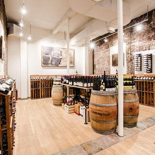 Imagen de bodega de estilo americano, grande, con suelo de madera clara, botelleros y suelo beige
