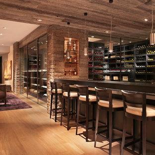Bild på en stor funkis vinkällare, med ljust trägolv, vinhyllor och beiget golv