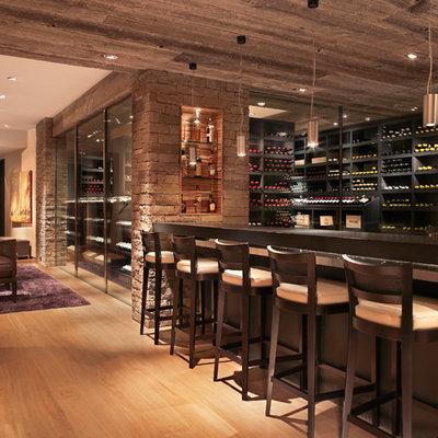 Example of a large trendy light wood floor and beige floor wine cellar design in Denver with storage racks