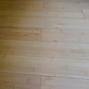 Exemple d'une petit cave à vin tendance avec un sol en bambou et des casiers.