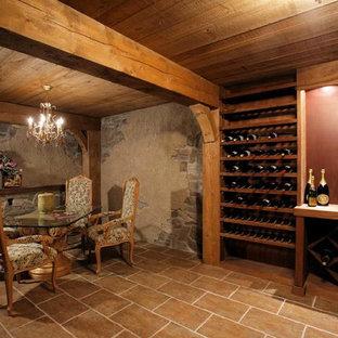 Cette image montre une très grand cave à vin traditionnelle avec un sol en travertin, un présentoir et un sol marron.