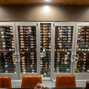 Réalisation d'une cave à vin design de taille moyenne avec sol en stratifié, des casiers et un sol gris.