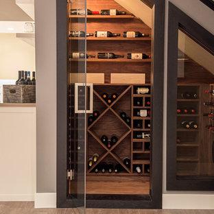 Idéer för en liten modern vinkällare, med ljust trägolv och vindisplay