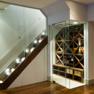 This is an example of a contemporary wine cellar in London with white floors.