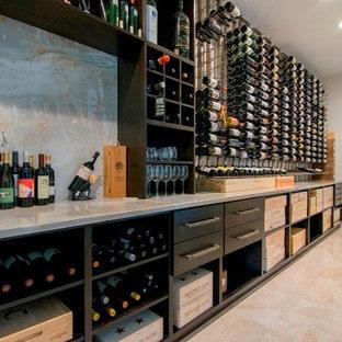 Cette photo montre une grand cave à vin tendance avec un sol en marbre, des casiers et un sol beige.