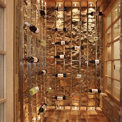 Wine cellar - coastal medium tone wood floor and beige floor wine cellar idea in Orange County with display racks