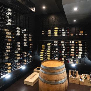 Imagen de bodega clásica renovada, pequeña, con botelleros y suelo negro