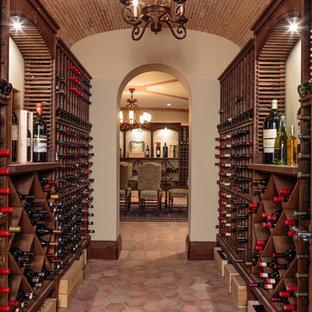 Bild på en mycket stor medelhavsstil vinkällare, med klinkergolv i terrakotta, vinhyllor och rött golv