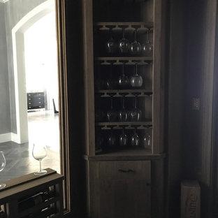 Imagen de bodega rústica, grande, con suelo de ladrillo, botelleros y suelo gris