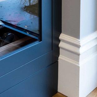 Ispirazione per una grande cantina moderna con pavimento in legno massello medio, rastrelliere portabottiglie e pavimento marrone