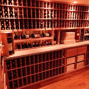 Exemple d'une grand cave à vin romantique avec un sol en bois clair, des casiers et un sol orange.