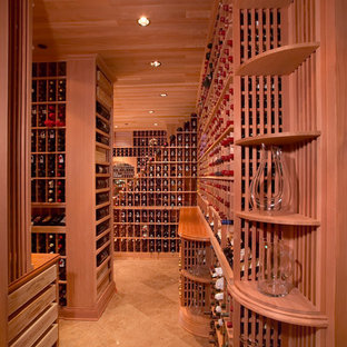 Photo of a large vintage wine cellar in Los Angeles with terracotta flooring and display racks.