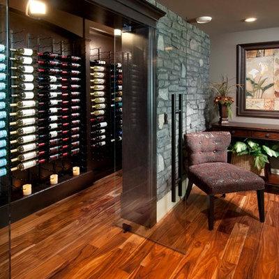 Example of a mid-sized classic medium tone wood floor and orange floor wine cellar design in Calgary with display racks