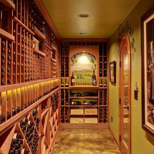 シアトルの巨大な地中海スタイルのおしゃれなワインセラー (コンクリートの床、ワインラック、黄色い床) の写真
