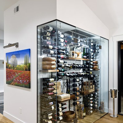 Example of a trendy light wood floor wine cellar design in Denver with storage racks