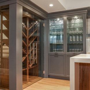 Ejemplo de bodega clásica renovada, de tamaño medio, con suelo de madera clara, vitrinas expositoras y suelo marrón
