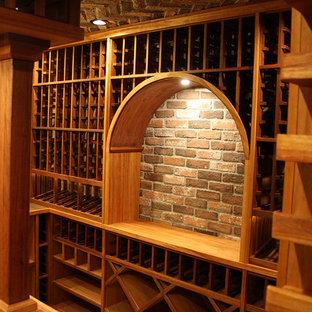 Foto på en stor medelhavsstil vinkällare, med tegelgolv och vinhyllor