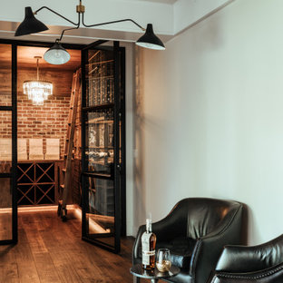 Mid-sized eclectic medium tone wood floor and brown floor wine cellar photo in Portland with storage racks