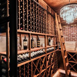 Foto di una cantina eclettica di medie dimensioni con pavimento in legno massello medio, rastrelliere portabottiglie e pavimento marrone