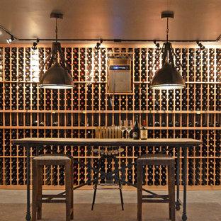Idée de décoration pour une grande cave à vin urbaine avec béton au sol et des casiers.