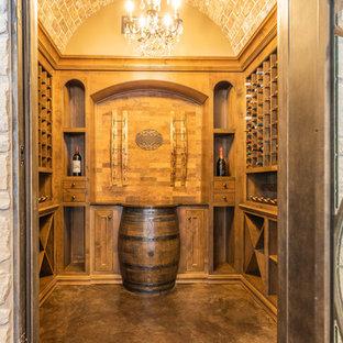Foto de bodega clásica, de tamaño medio, con suelo de cemento, botelleros y suelo marrón