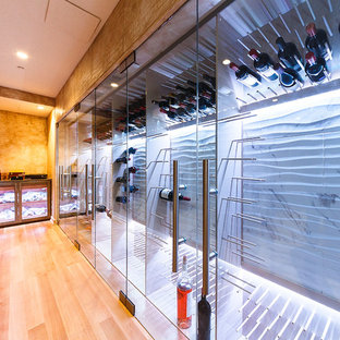 This is an example of a large contemporary wine cellar in New York with light hardwood flooring and display racks.