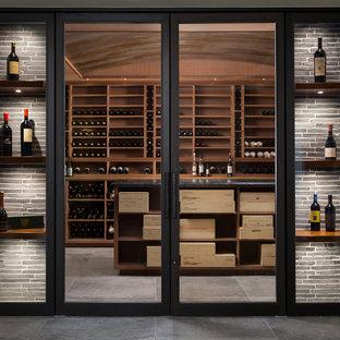 Inspiration för en mellanstor funkis vinkällare, med betonggolv, vinhyllor och grått golv