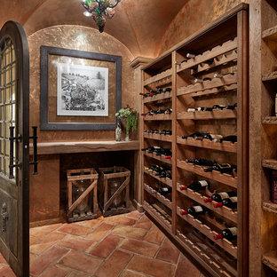 Foto de bodega rústica, grande, con suelo de baldosas de terracota, botelleros y suelo marrón
