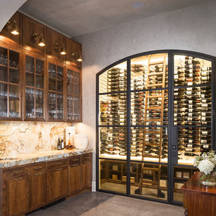 Example of a mid-sized transitional concrete floor and gray floor wine cellar design in Austin with storage racks