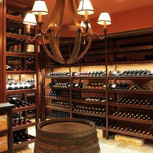 Cette photo montre une grand cave à vin chic avec un sol en calcaire, des casiers et un sol beige.