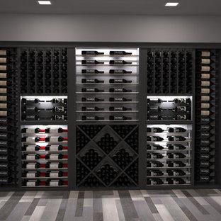 Immagine di una grande cantina moderna con parquet chiaro e rastrelliere portabottiglie
