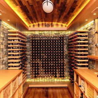 Imagen de bodega clásica renovada con suelo de madera en tonos medios y botelleros