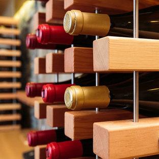 Diseño de bodega contemporánea, de tamaño medio, con botelleros y suelo de madera clara