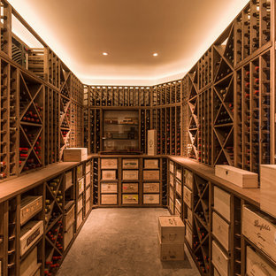 This is an example of a medium sized contemporary wine cellar in London with concrete flooring, cube storage and grey floors.