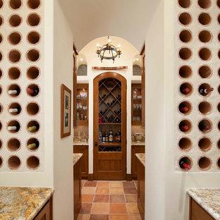 Foto på en medelhavsstil vinkällare, med klinkergolv i terrakotta, vinhyllor och orange golv