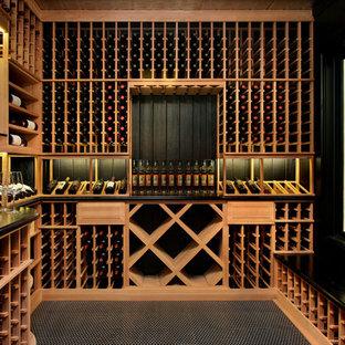 Réalisation d'une cave à vin tradition avec des casiers et un sol noir.