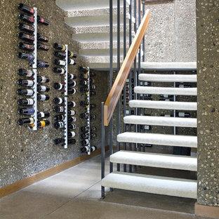 Idee per una cantina contemporanea di medie dimensioni con pavimento in cemento, rastrelliere portabottiglie e pavimento grigio