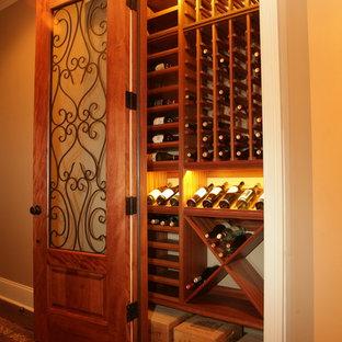 Idées déco pour une petit cave à vin classique avec un sol en bois brun, des casiers et un sol marron.