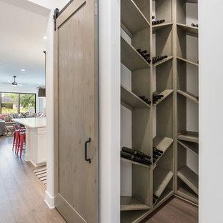 Diseño de bodega de estilo de casa de campo, de tamaño medio, con suelo de madera en tonos medios, botelleros de rombos y suelo marrón