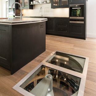 Design ideas for a small contemporary wine cellar in London with light hardwood flooring.