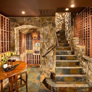 Cette photo montre une grand cave à vin chic avec des casiers, un sol en ardoise et un sol multicolore.