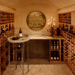 Example of a mid-sized tuscan terra-cotta floor and beige floor wine cellar design in Santa Barbara with storage racks