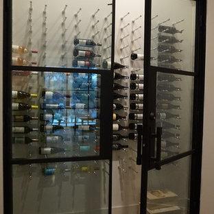Foto de bodega minimalista, de tamaño medio, con suelo de madera en tonos medios y botelleros