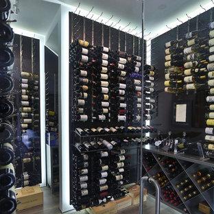 Aménagement d'une grand cave à vin contemporaine avec un sol en carrelage de porcelaine, des casiers et un sol gris.